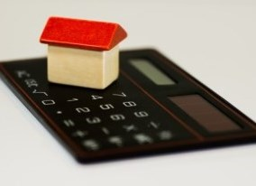 Calculator with wood block house on top