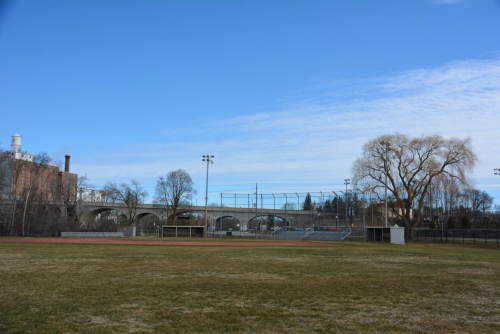 Park with baseball diamond and a bridge and old industrial factory in background