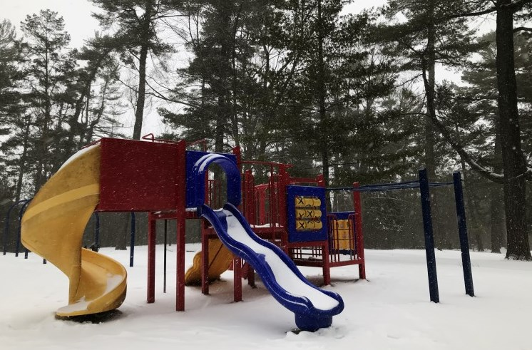 Playground structure covered in snow with trees behind
