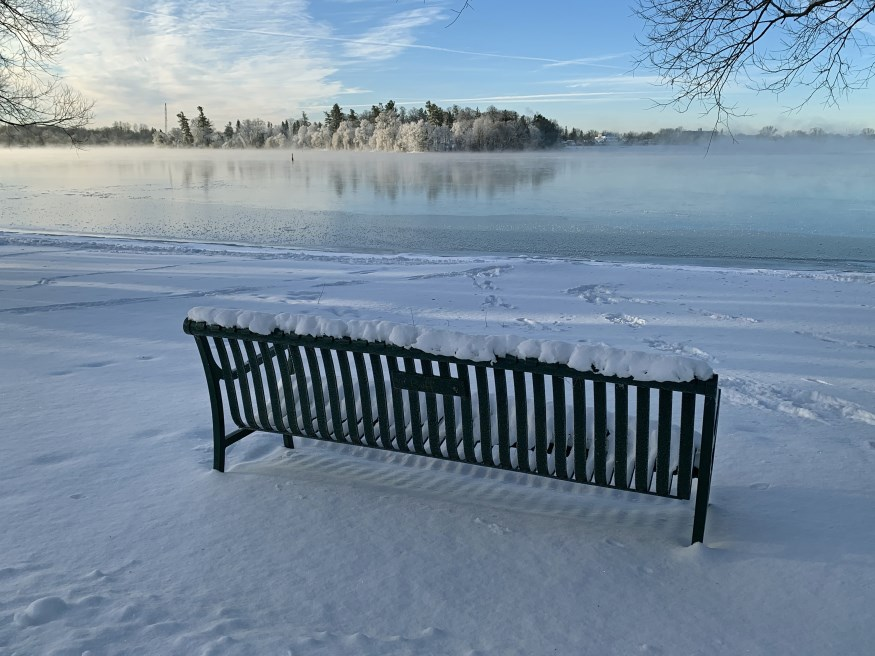 Winter landscape, park bench covered in snow overlooking a lake with frost covered trees on the other shore