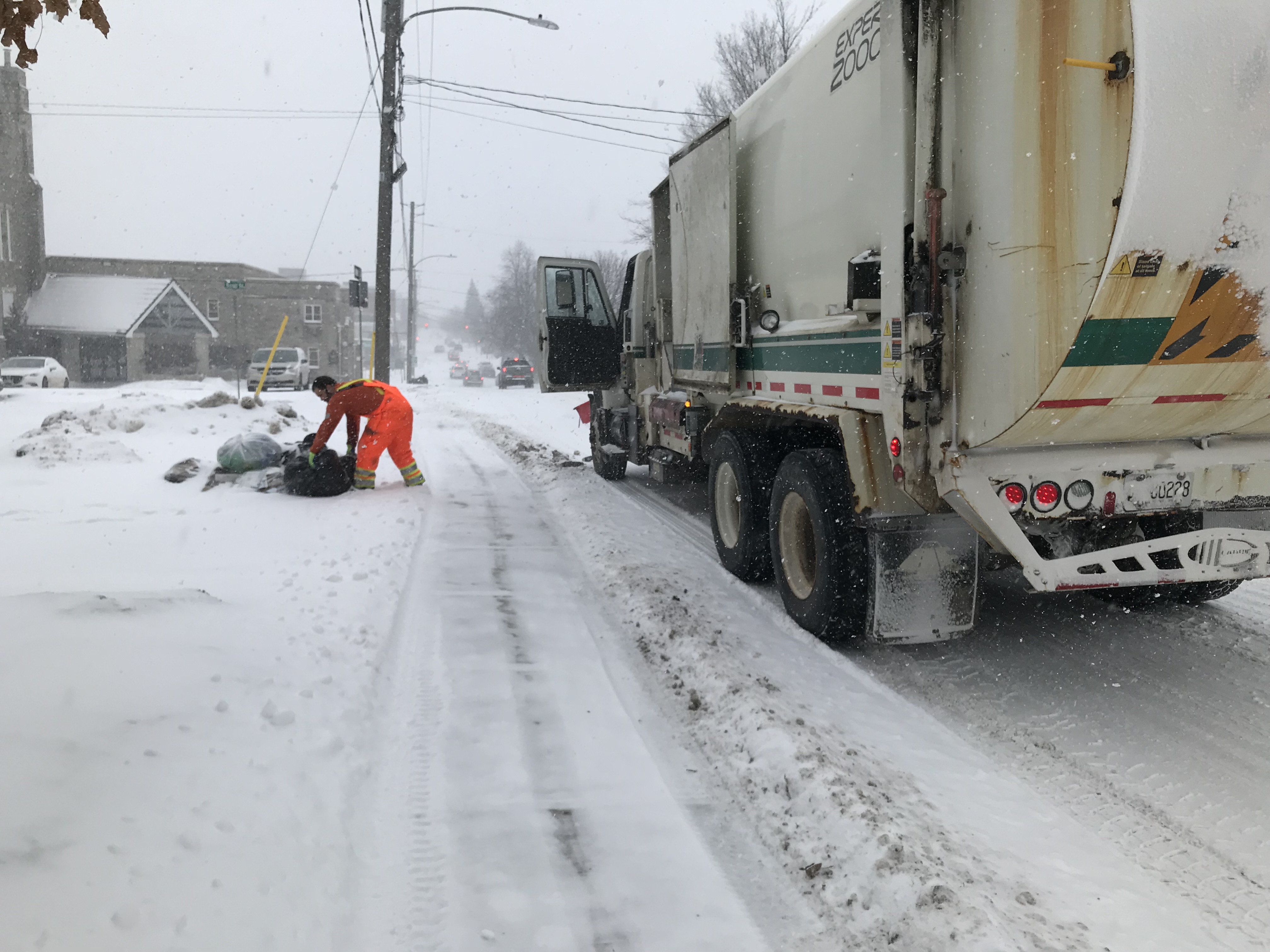 snowy street, waste collection vehicle stopped on side of street as worker picks up recycling