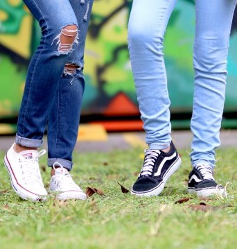 Legs and low top sneakers of two young adults