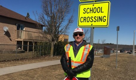 Crossing guard standing at school crossing sign