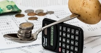 Image of spoon balancing money on one side and food on the other over a calculator.