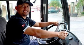 Transit driver sitting in drivers seat of a bus, smiling