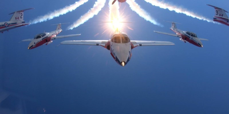 Snowbirds in flight formation with sunburst
