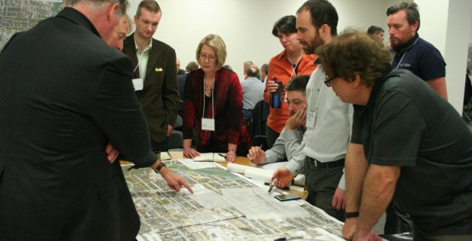 People around a table with a map discussing urban design