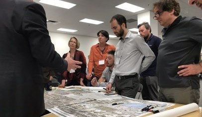 Group discussion with people standing around a table discussing a map