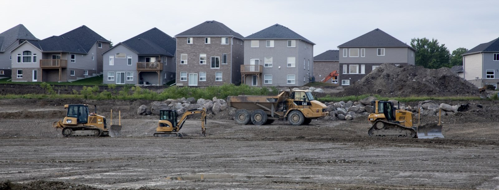 subdivision construction with construction vehicles and new houses