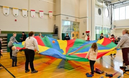 event at Wellness Centre during Snofest featuring families playing in gym with parachute