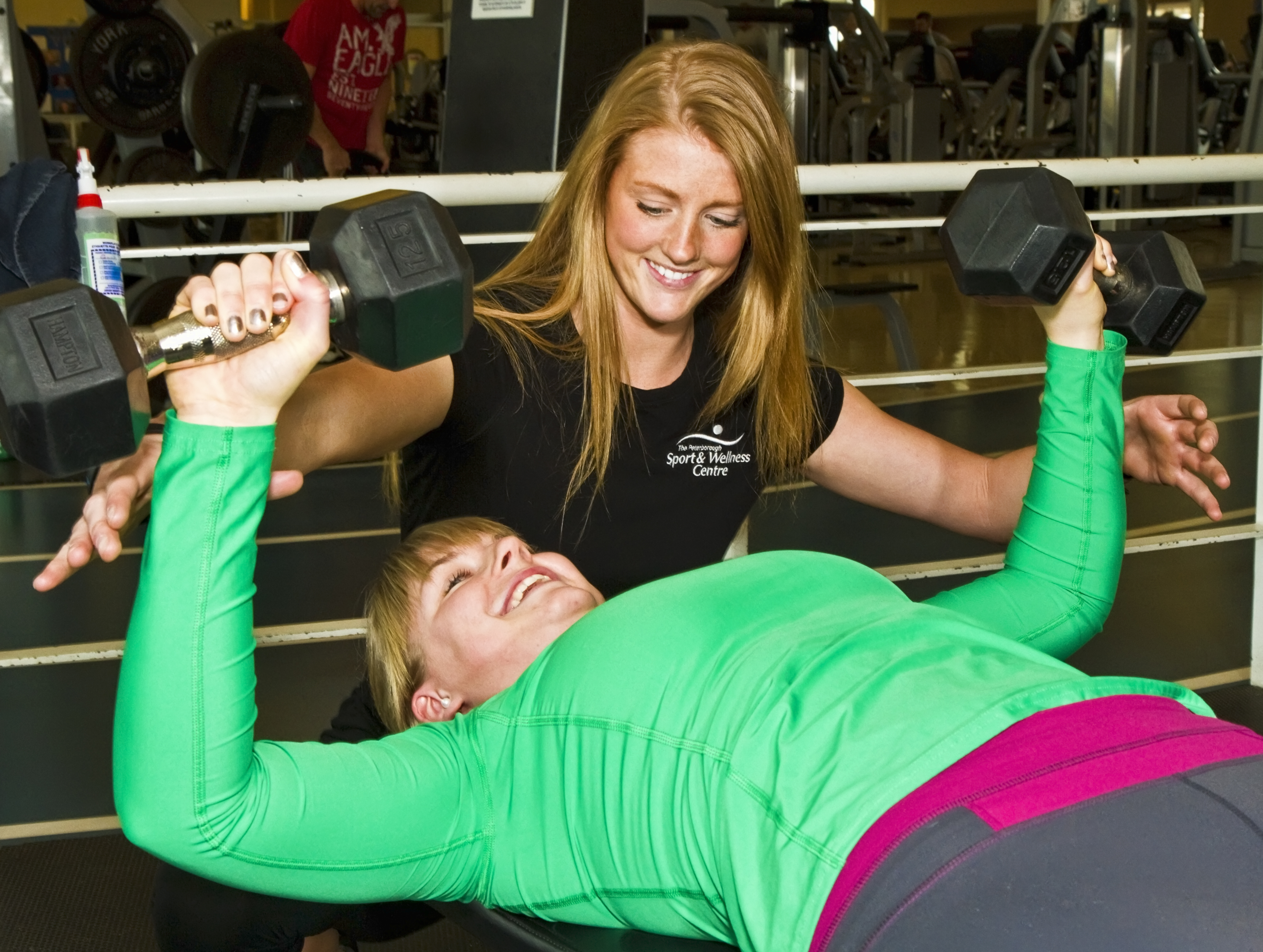 Woman doing chest press with help from trainer