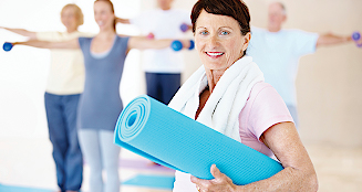 Smiling woman holding yoga mat