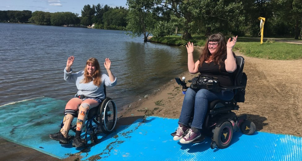 Two people in wheelchairs using an accessible mat on a beach