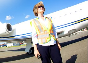 Woman in safety vest in front of landed plane
