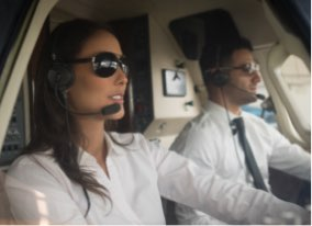 Man and woman flying airplane with headset on