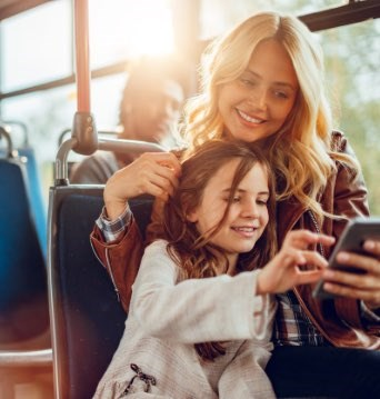Mom and daughter riding the bus looking at a phone